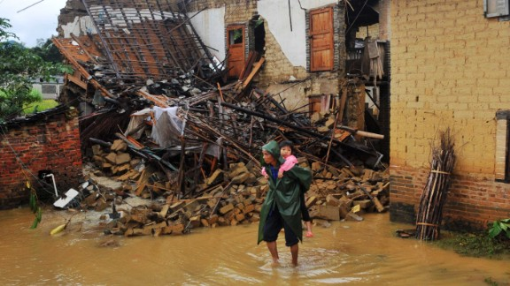 A woman carries a child through a flooded street in Yong