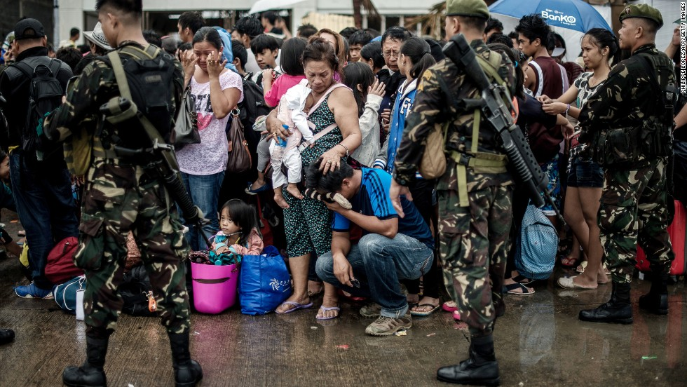 A woman comforts a crying relative as a plane leaves the Tacloban airport November 12.