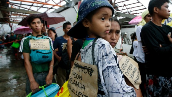 Typhoon survivors line up November 12 in hopes of boarding a military transport plane out of Tacloban.