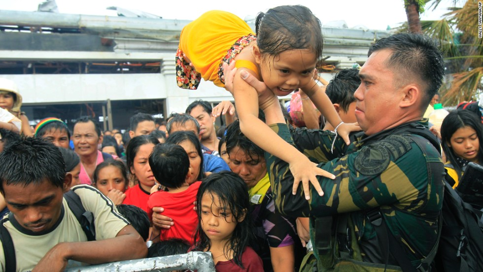 Philippine military personnel try to prioritize children and women first as people wait for evacuation flights November 12 in Tacloban.