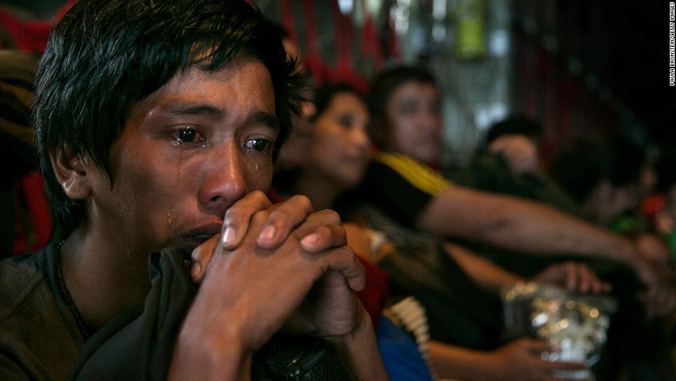 A man sits crying on a packed aircraft in Tacloban on November 12.