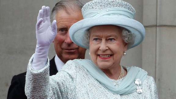 The Queen waves from the balcony of Buckingham Palace as Charles, stands behind her, during the finale of the Queen