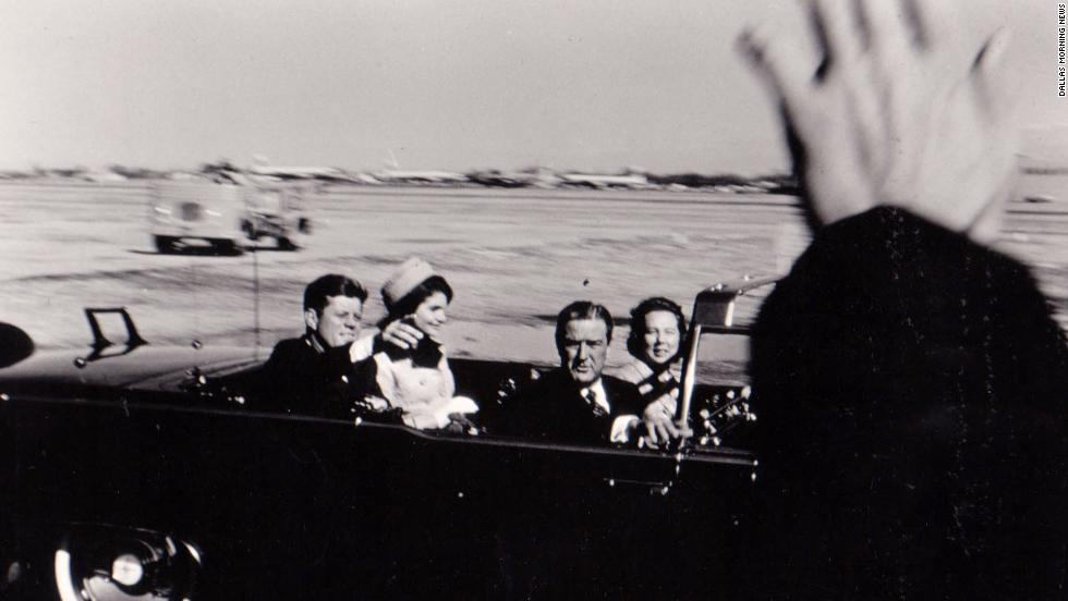 The Kennedys and Connallys leave Love Field with Secret Service Agent Bill Greer driving the presidential limousine. The motorcade is on the way to the Trade Mart, where Kennedy is to speak at a sold-out luncheon.