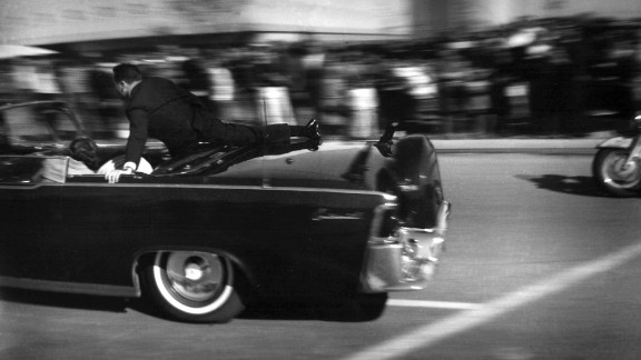 The limousine carrying the mortally wounded President races toward the hospital seconds after three shots are fired. Two bullets hit Kennedy and one hit Connally.  Hill rides on the back of the car as the wives cover their stricken husbands.