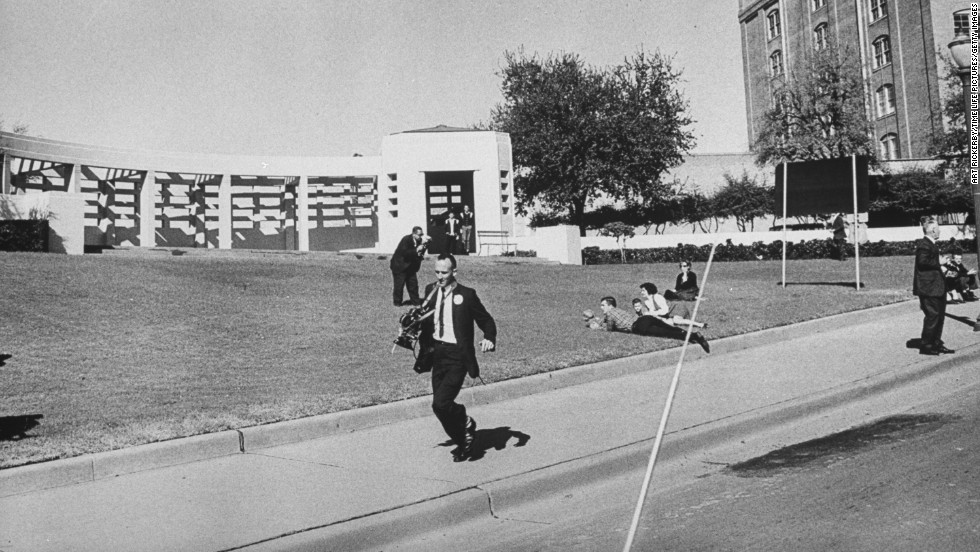 Photographers are seen running shortly after the shooting.