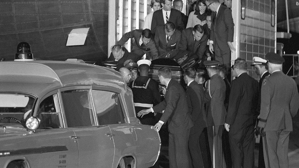The casket containing the body of President Kennedy is moved to a Navy ambulance from the presidential plane. Jacqueline Kennedy and Attorney General Robert Kennedy stand behind on the elevator.
