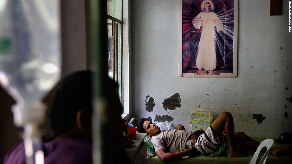 An injured man in Tacloban rests beneath a picture of Jesus Christ on November 13.