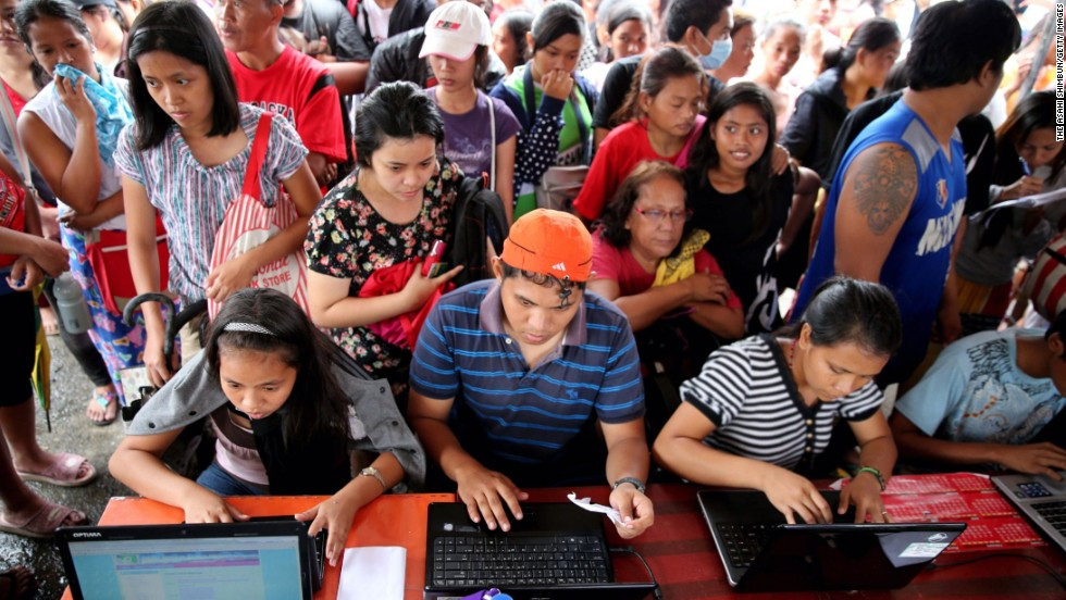 Evacuees send e-mails to their family members and relatives November 12 at a free Internet cafe in Tacloban set up by the Philippine government.