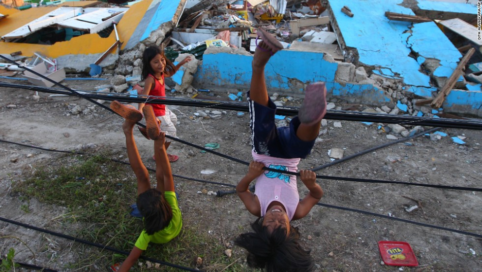 Children play with fallen power lines near a damaged school in Guiuan on November 14.
