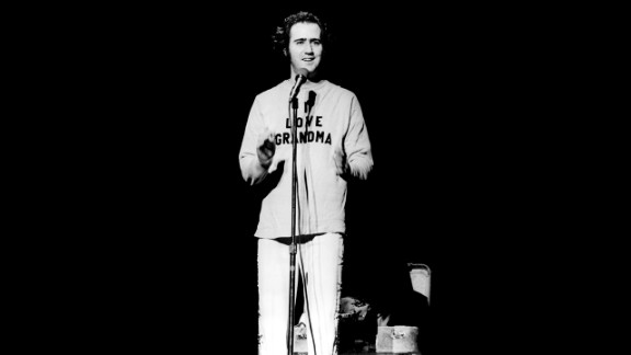 """Andy Kaufman onstage in 1977, wearing a """"I love grandma"""" sweater after doing one of his trademark Elvis impersonations."""