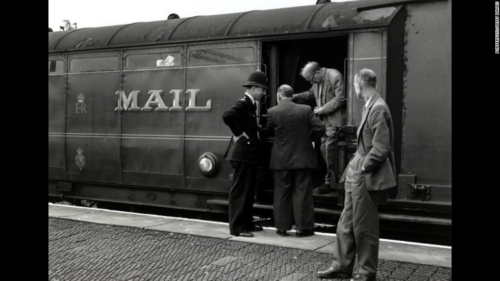 Detectives inspecting the Royal Mail train from which more than £2.5 million was stolen. The Great Train Robbery took place in Buckinghamshire on August 8,1963, when the train from Glasgow to London was halted by a gang.