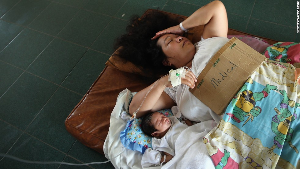 A woman and her newborn baby lie on the floor of a Tacloban hospital on November 15.