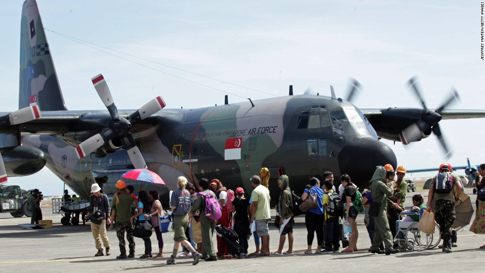 Residents wait to board a Singaporean cargo plane at the Tacloban airport on November 15. Many survivors have converged on the city's airport to wait for flights.