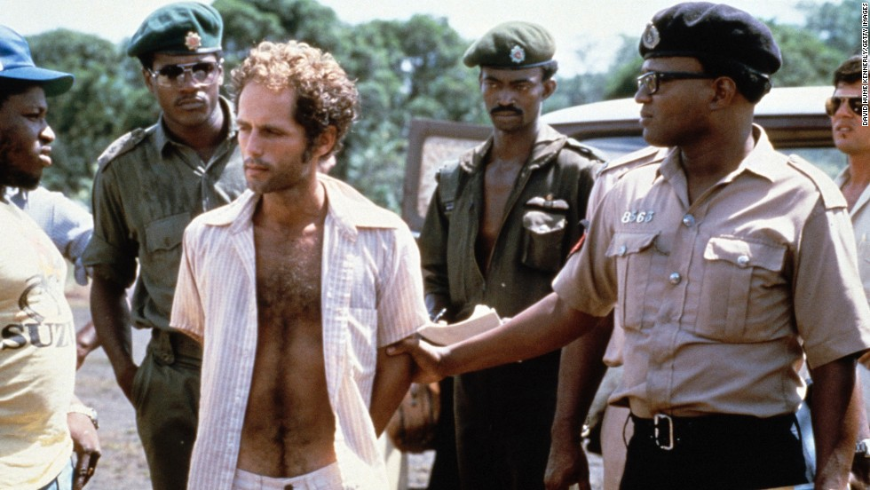 People's Temple follower Larry Layton, center, stands with police following his arrest in connection with the shooting at the remote Guyana airstrip. Layton was convicted in 1986 by a federal jury in San Francisco of conspiring in Ryan's murder and aiding and abetting in the attempted murder of Richard Dwyer, a U.S. diplomat wounded in the attack.