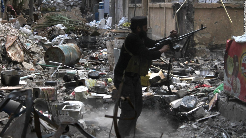 A rebel fighter fires during clashes with government forces in Deir Ezzor on November 11.