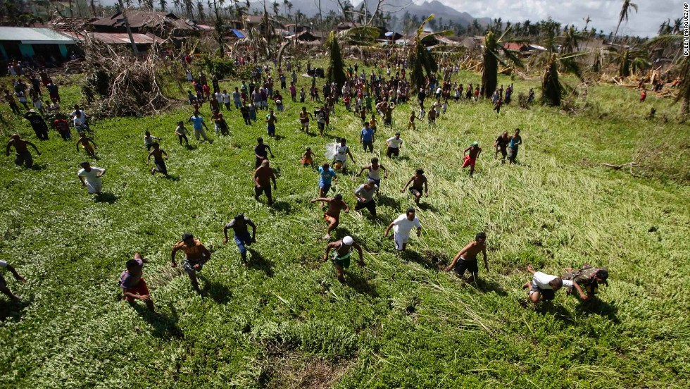 Villagers isolated by the typhoon scramble for relief goods being dropped by the Philippine Air Force on Friday, November 15, in La Paz.
