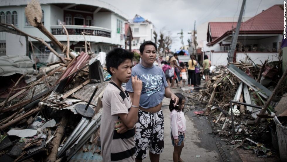 Survivors of the typhoon stand in a Tanauan street partially blocked by debris November 16.