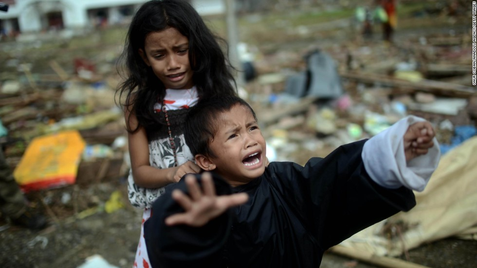 Two Filipino children cry as their mother, using a refrigerator as a boat, tries to move the family to a neighboring island near Tacloban on November 16. Aid workers would not let the woman and her children travel this way.