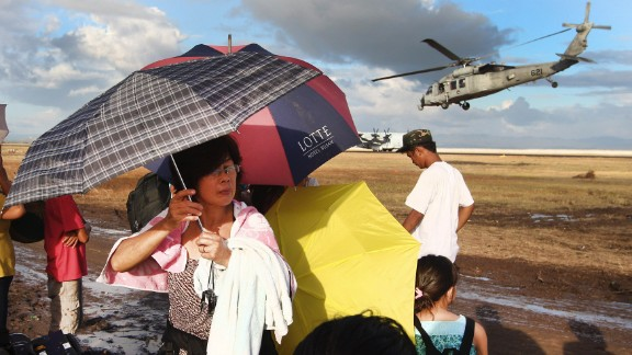Typhoon survivors wait for an evacuation flight as a U.S. Navy helicopter takes off at the Tacloban airport Sunday, November 17.