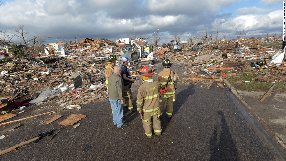 Firefighters stand in the middle of the street after a tornado leveled at homes in Washington, Illinois, on November 17.