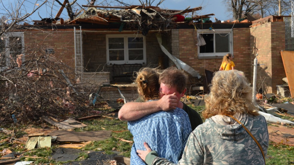 Ray Baughman embraces family shortly after his home was destroyed by a tornado south of Peoria in Pekin, Illinois, on November 17.