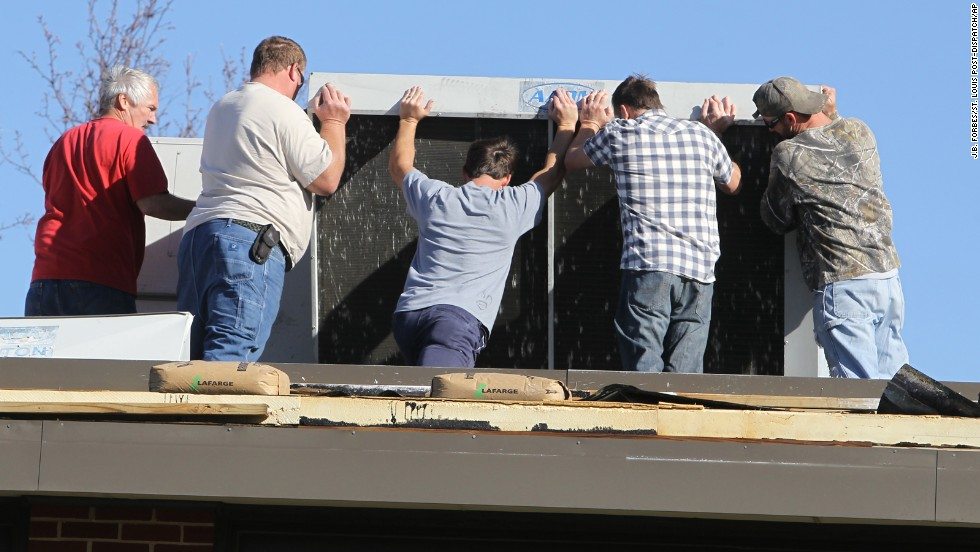 Volunteers try to reposition the HVAC unit on top of Heritage Primary Elementary School in Wentzville, Missouri, on November 17. Board members, staff and teachers came to the school to help with the cleanup after a storm tore off parts of the roof. Wentzville is about 40 miles west of St. Louis.