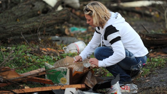 Maranda Souders picks up a crystal bowl and cup while searching through debris from her grandmother