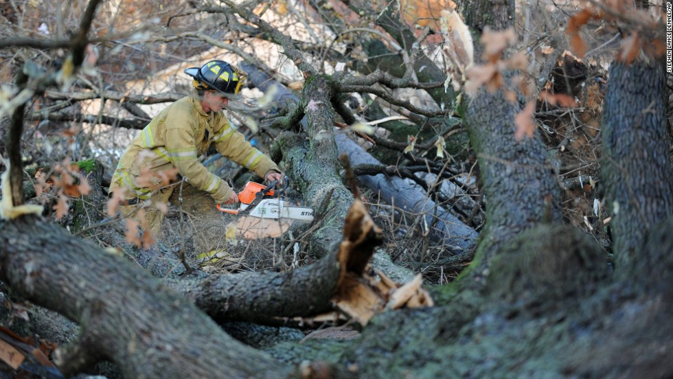 A firefighter works to clear a tree from a street in Brookport, Illinois, on November 17.