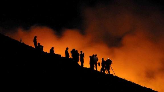 Reporters watch lava flow down Etna in 2001.