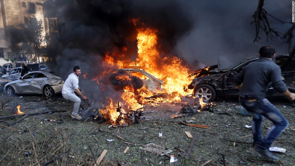Men attempt to recover bodies from burning cars November 19 in Beirut.