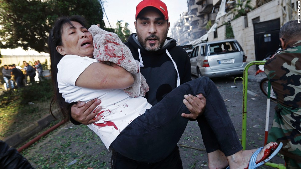 An injured woman is carried away from the scene in Beirut on November 19.