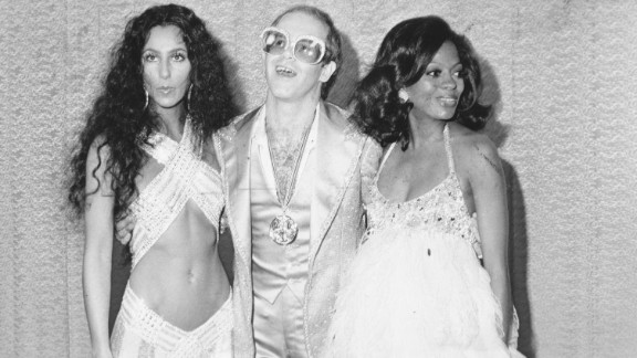 John poses for a photo with Cher and Diana Ross in the mid-1970s.