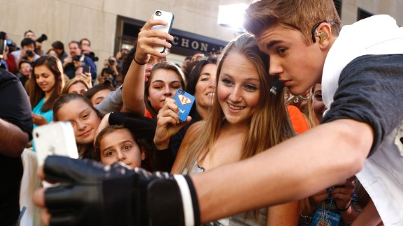 Singer Justin Bieber takes a selfie with a fan before appearing on NBC
