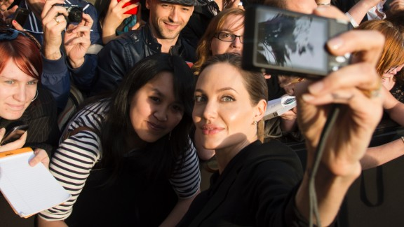 Actress Angelina Jolie takes a photo of herself with a fan