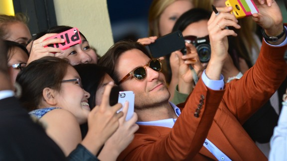 "Actor Bradley Cooper poses for selfies with eager fans at the Los Angeles premiere of ""The Hangover Part III."""