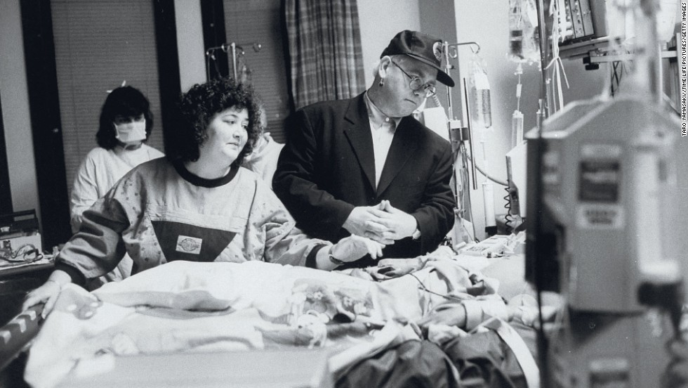 John stands by the bed of AIDS patient Ryan White at a Florida hospital in 1990. Two years later, the singer established the Elton John AIDS Foundation.