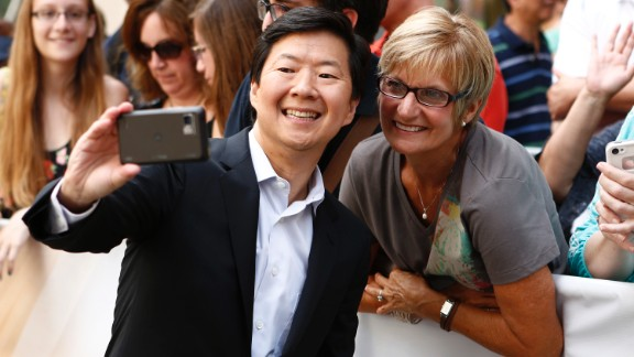 Actor Ken Jeong takes a photo with a fan before appearing on NBC