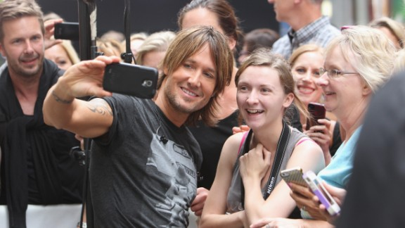 Musician Keith Urban takes a selfie with a fan before performing at NBC