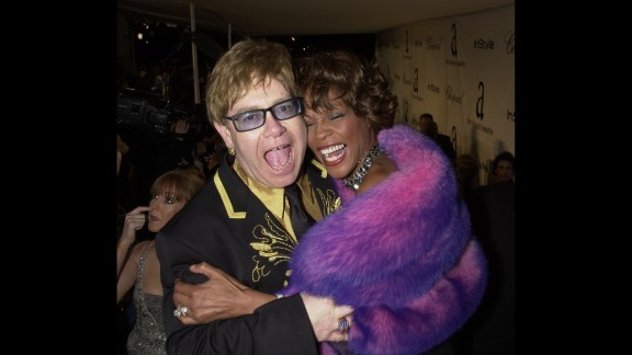 """Whitney Houston hugs John at the Academy Awards in 2001. A few years earlier, John had won an Oscar for """"Can You Feel The Love Tonight,"""" his song in Disney's """"The Lion King."""""""