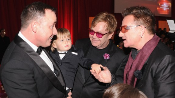 U2 singer Bono, right, talks with John, Furnish and their son Zachary at an Academy Awards viewing party in 2013.