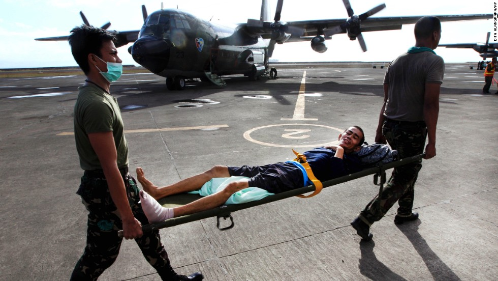 Philippine military personnel carry an injured survivor to an evacuation flight at the Tacloban airport November 19.