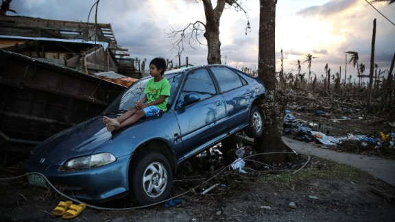 A boy sits on a car amid the debris in Leyte, Philippines, on Monday, November 18.