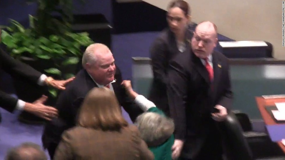 Ford accidentally knocks down Councilor Pam McConnell, in green, as he runs toward hecklers at City Hall in Toronto on Monday, November 18. That month, the city council stripped him of most of his power as mayor.