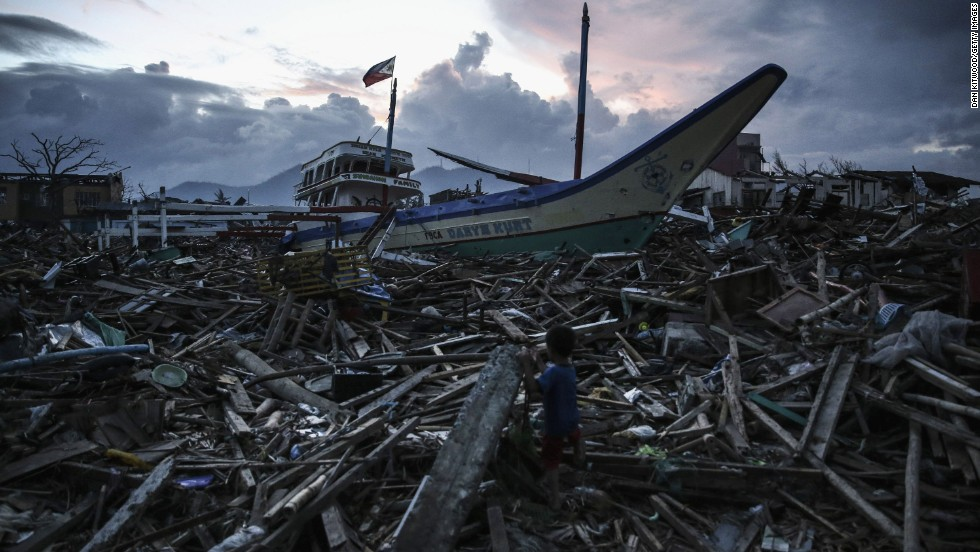 A boy climbs across debris in Tacloban on November 20.