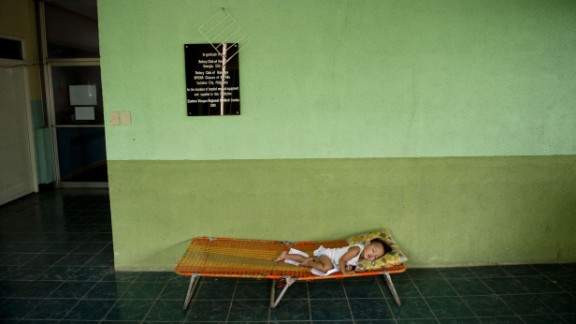 A child sleeps in a hallway outside the overcrowded children