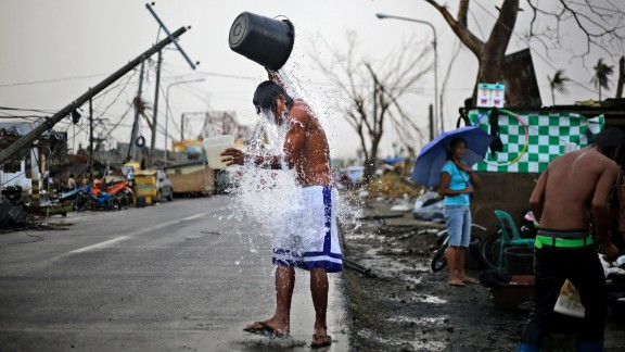 A young Filipino takes a shower on the side of a road in Tacloban, on Thursday, November 21.