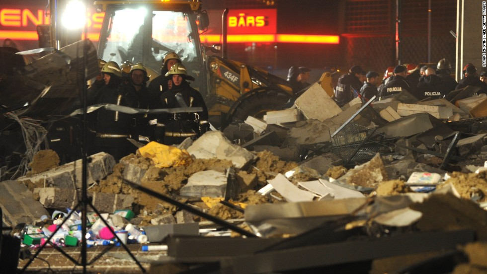 Rescue workers stand amid the debris from the collapse.