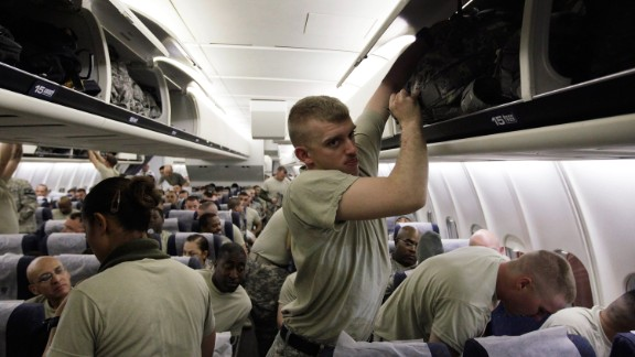 U.S. Army soldiers from the 2-82 Field Artillery, 3rd Brigade, 1st Cavalry Division, place their bags in the overhead bins as they wait for their plane to take off for the flight home to Fort Hood, Texas after being part of one of the last American combat units to exit from Iraq on December 16, 2011 in Kuwait City, Kuwait.