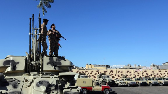 Militiamen prepare to vacate their Tripoli quarters on Thursday, as part of a government decision to remove the armed groups from the capital.