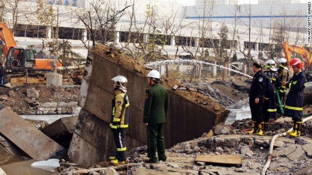 Chinese rescuers search for victims after an oil pipeline exploded in Qingdao on November 22.